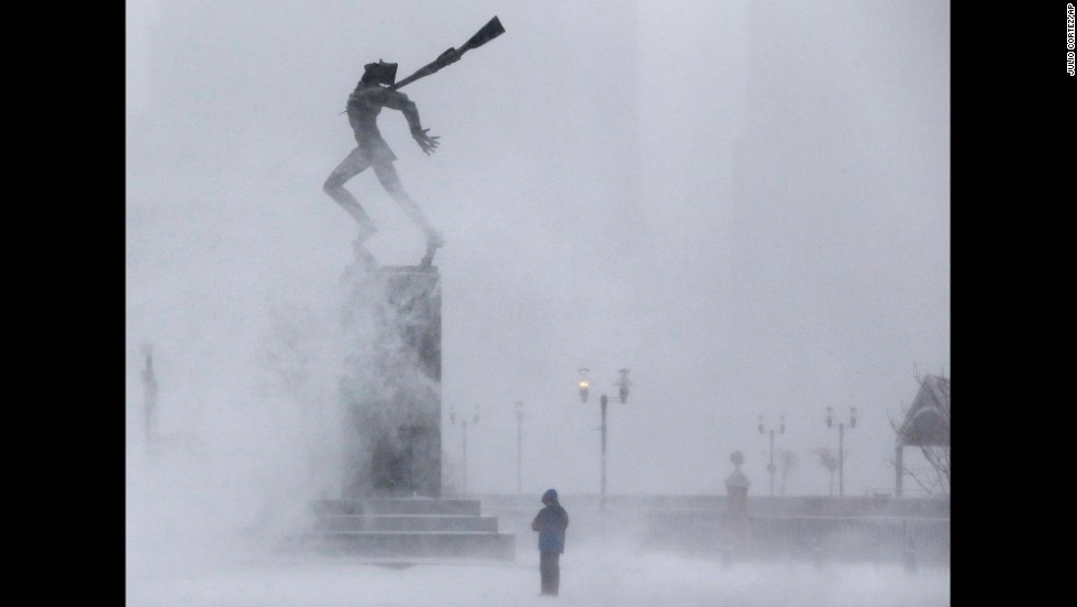 Wind kicks up snow January 21 in front of a statue in Jersey City, New Jersey.