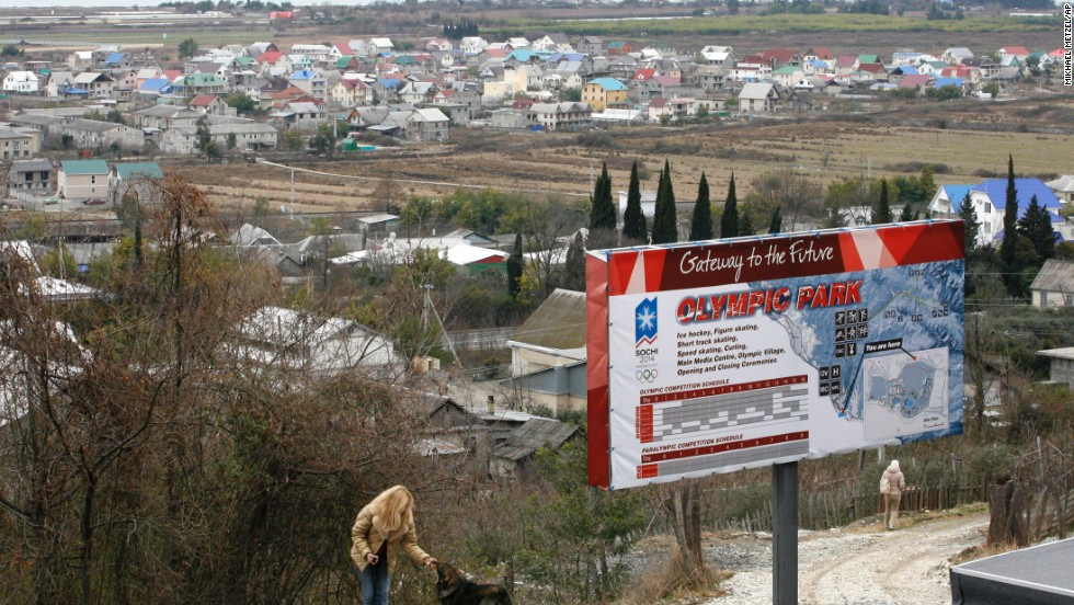 In the Imeretinskay Valley, a woman plays with a dog in February 2007, near an advertisement for the Olympic Park soon to be built in the area. Organizers of the Sochi Olympics say they want these Games to be the greenest, most environmentally aware games ever staged.