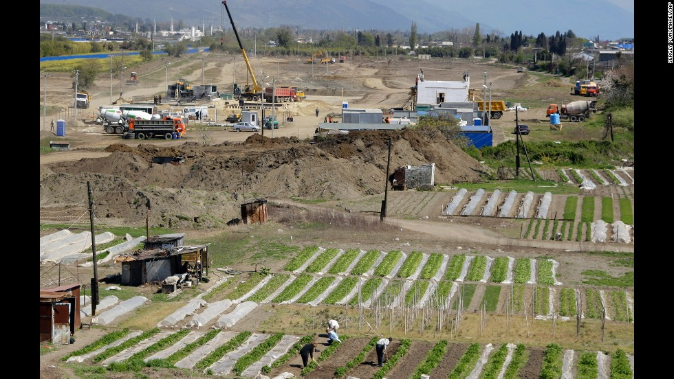 People work on their vegetable gardens near the construction site of the Olympic facilities in the Imeretinskaya Valley in April 2009.