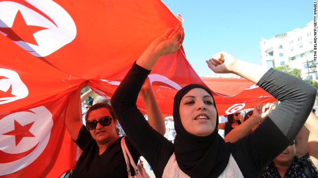 Tunisian women shoot slogan during a demonstration in solidarity with policemen and security forces and to denounce the death of six policemen in a clash last week on October 28, 2013 on Habib Bourguiba Avenue in Tunis. Hundreds of protesters took part in the protest outside the interior ministry in Tunis in what was billed as a 'symbolic national funeral' for slain members of the security forces, an AFP journalist said. AFP PHOTO / FETHI BELAID (Photo credit should read FETHI BELAID/AFP/Getty Images)