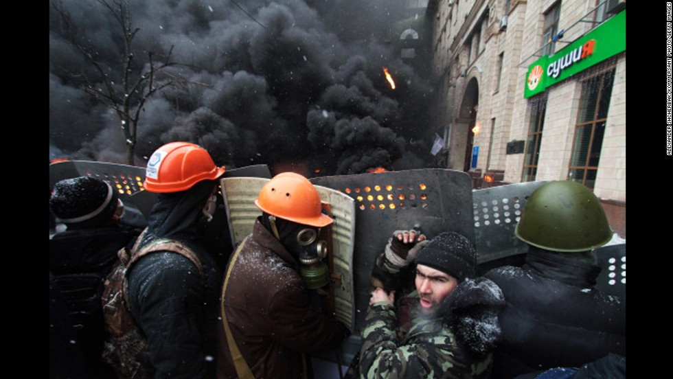 Protesters are seen in front of burning tires on Grushevsky Street.