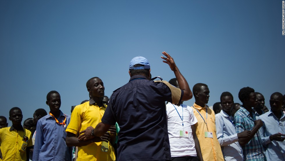 A United Nations peacekeeper gestures as South Sudanese students wait to walk back to a camp for internally displaced people after taking an English exam at a United Nations base in Juba on Monday, January 13.