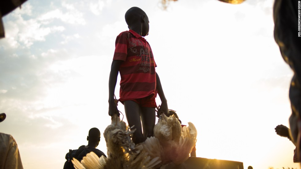 A boy carries chickens off a boat arriving in the village of Minkammen in Awerial county, South Sudan, on Saturday, January 11.
