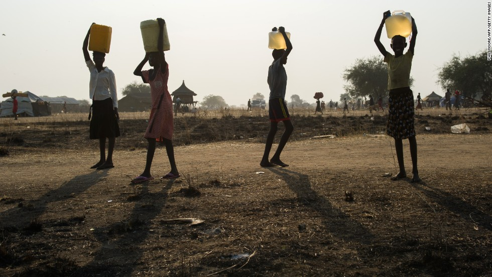 Internally displaced children carry water in Minkammen on January 10.