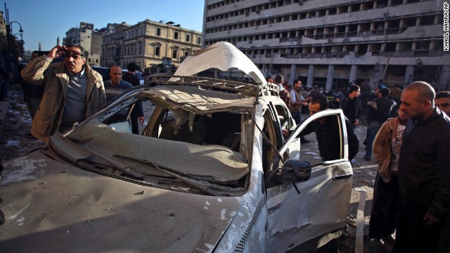 People inspect a destroyed taxi cab at the site of the explosion.