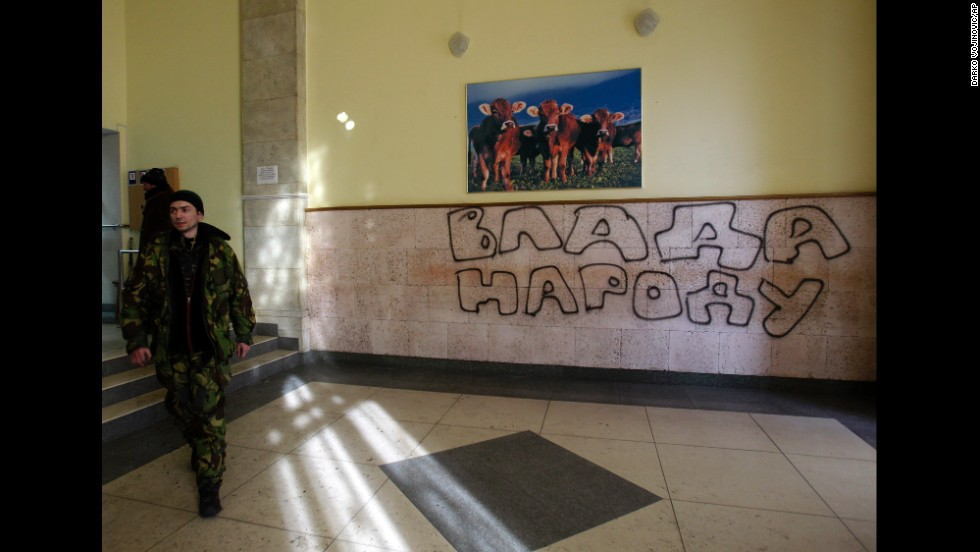 "A protester passes past graffiti that reads ""Government for People"" in the Ministry of Agricultural Policy building in Kiev on January 24."