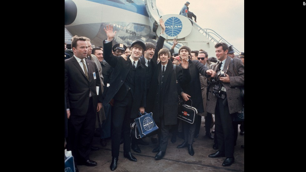 The band waves to cameras at John F. Kennedy International Airport.