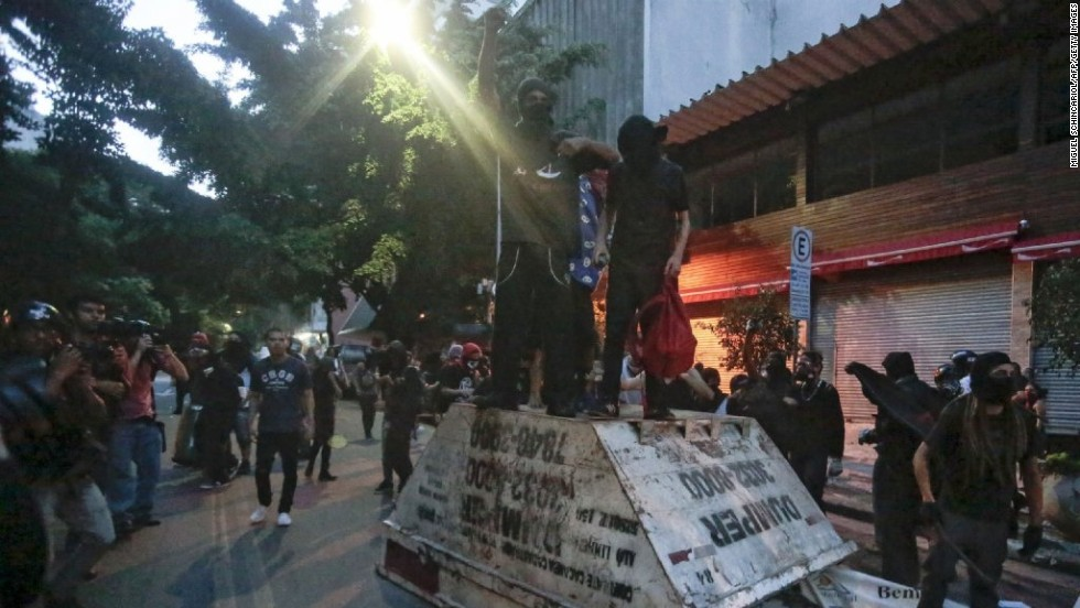Demonstrators stand on top of an overturned garbage container.