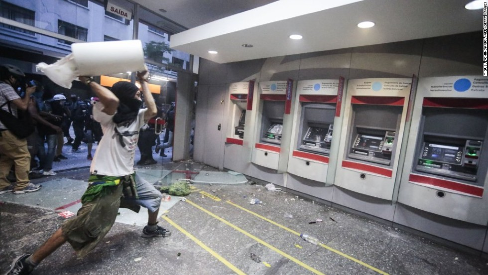 A protester throws debris at a line of ATMs.
