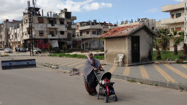 A Syrian woman walks with her child in the Baba Amr neighbourhood of the central Syrian city of Homs on February 11, 2013.