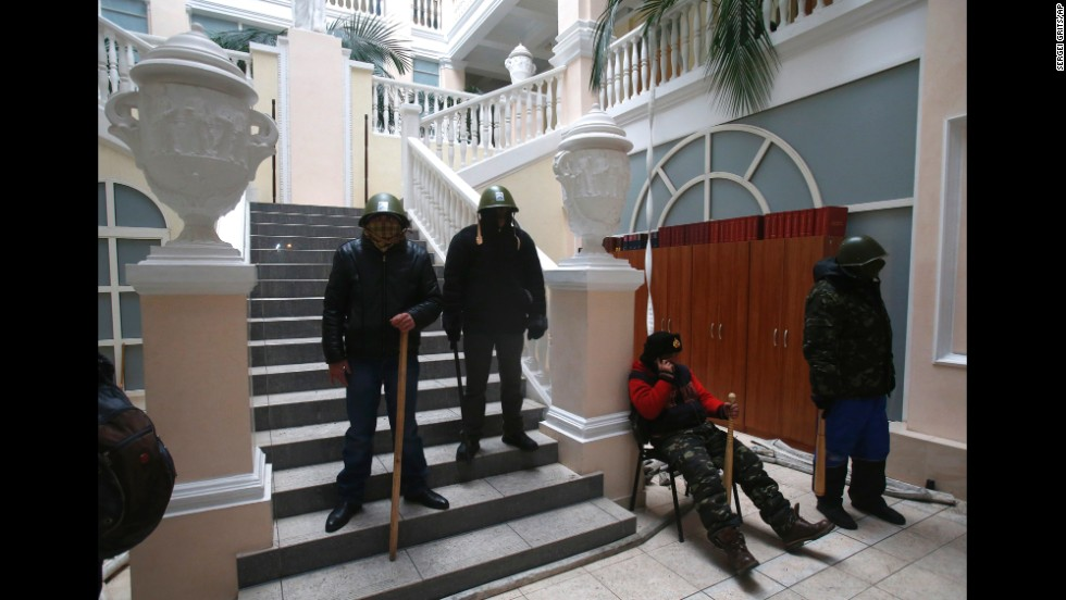 Protesters stand guard inside the Ukraine Justice Ministry in Kiev on January 27. Demonstrators later left the building because they didn't want to create any difficulties in negotiations between the government and opposition, a protest leader said. Protesters repositioned themselves outside and blocked access to the building, the leader said.
