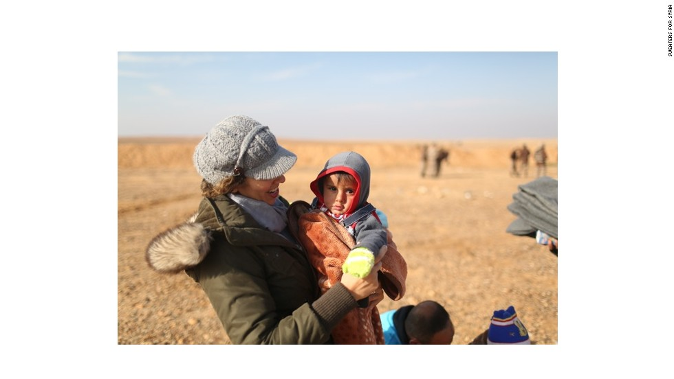 Ranya Alkadamani, who founded Sweaters for Syria, holds a Syrian refugee after he and his family just crossed the border into Jordan.