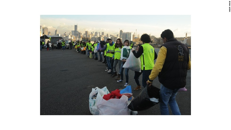 I AM NOT A TOURIST volunteers in Beirut, Lebanon form a human chain to load truck full of donated goods for Syrian refugees.