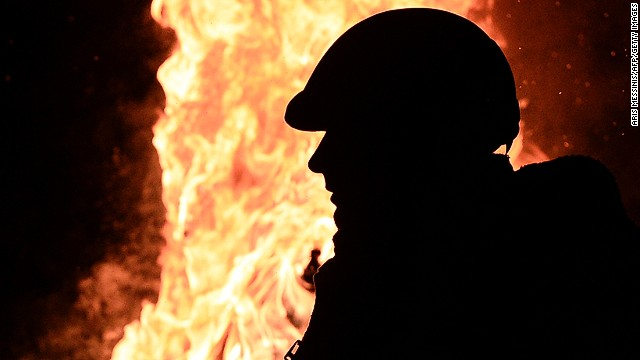An anti-government protester stand next to a fire to get warm at a road block in Kiev on January 26, 2014.