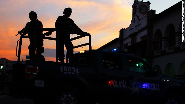 Mexican federal police patrol during a march for peace in Apatzingan, Michoacan State, Mexico, on January 18, 2014.