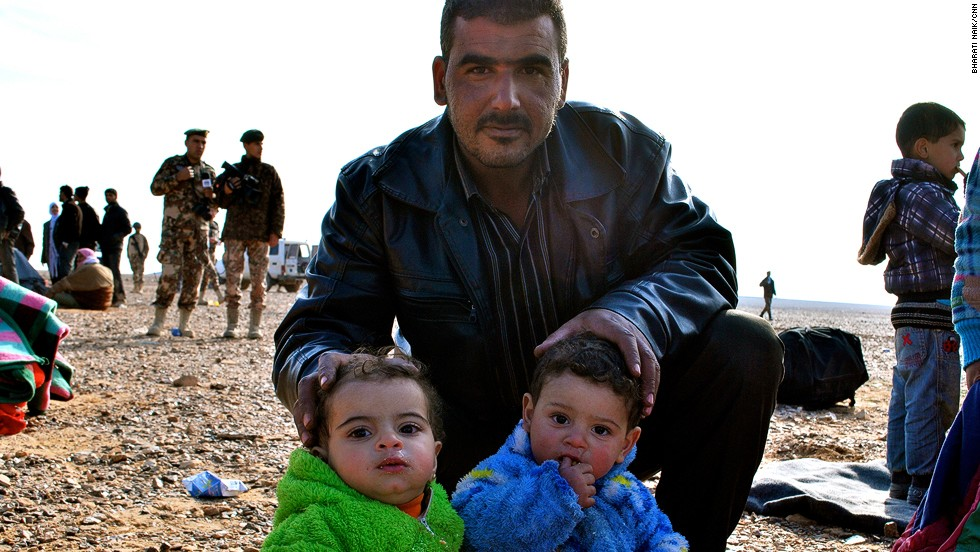 A father poses with his twins near the Jordanian border. The man told CNN he came across the border with about 10 other members of his family from the Damascus suburbs.