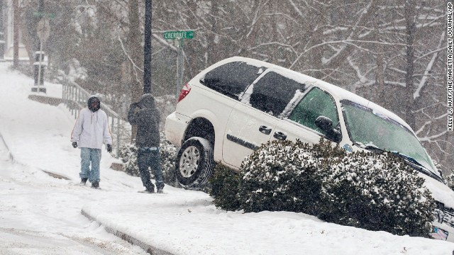 A vehicle ran off the road during a snow storm, Tuesday, Jan. 28, 2014 in Canton, Ga. A winter storm that would probably be no big deal in the North all but paralyzed the Deep South on Tuesday, bringing snow, ice and teeth-chattering cold, with temperatures in the teens in some places. (AP Photo/The Marietta Daily Journal, Kelly J. Huff/The Marietta Daily Journal/AP)  ATLANTA JOURNAL CONSTITUTION OUT; MAGS OUT; NO SALES