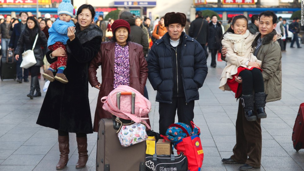 Li Canming (R) and Liu Shuxia (L) have lived in Beijing for 12 years. They're going back to Baotou, Inner Mongolia for Chinese New Year with their parents (center) and two children. The husband works in a factory making disposable tableware, while his wife does research for oilfields. Li is holding their 11-year-old daughter and Liu is holding their one-year-old son.