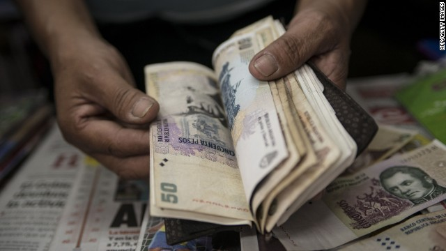 """A newsstand owner counts Argentine pesos in Buenos Aires on January 24, 2014. Argentina on Friday lifted restrictions in place since 2011 that limited the purchase of foreign currency, a day after the peso suffered its worst single-day dive since the 2002 financial crisis. The government has decided """"to authorize the purchase of dollars for holding or savings, """" said Jorge Capitanich, President Cristina Kirchner's cabinet chief. The restrictions had always been temporary and had served their purpose. TOPSHOTS/AFP PHOTO / LEO LA VALLELEO LA VALLE/AFP/Getty Images"""