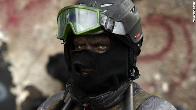 A masked Ukrainian anti-government protester stands at a roadblock in Kiev on January 29, 2014.