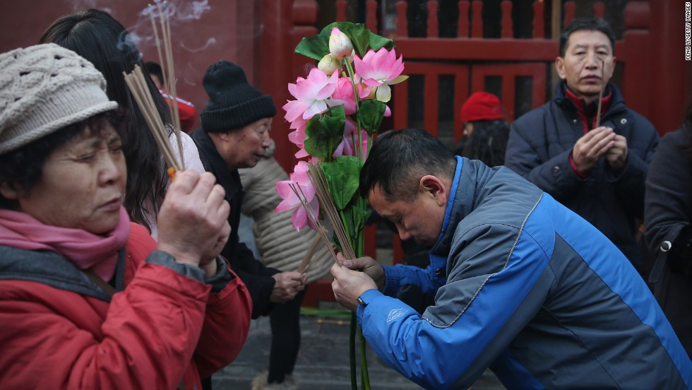 A crowd of people prays for good fortune outside the Yonghegong Lama Temple.