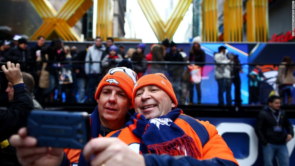 Denver Broncos fans photograph themselves during Super Bowl festivities in New York's Times Square on Friday, January 31.