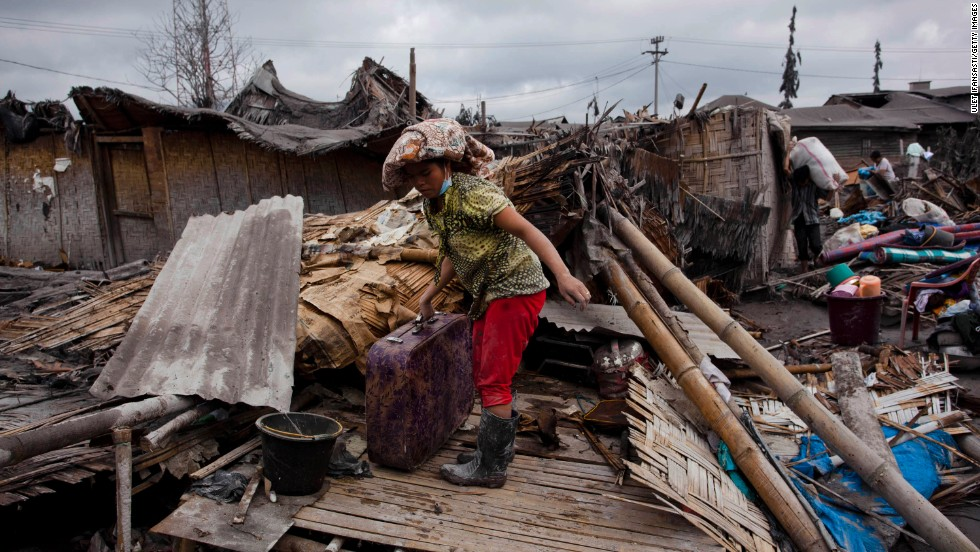 A villager looks for belongings among debris at a house damaged by ash and mud from eruptions of Mount Sinabung on January 12.