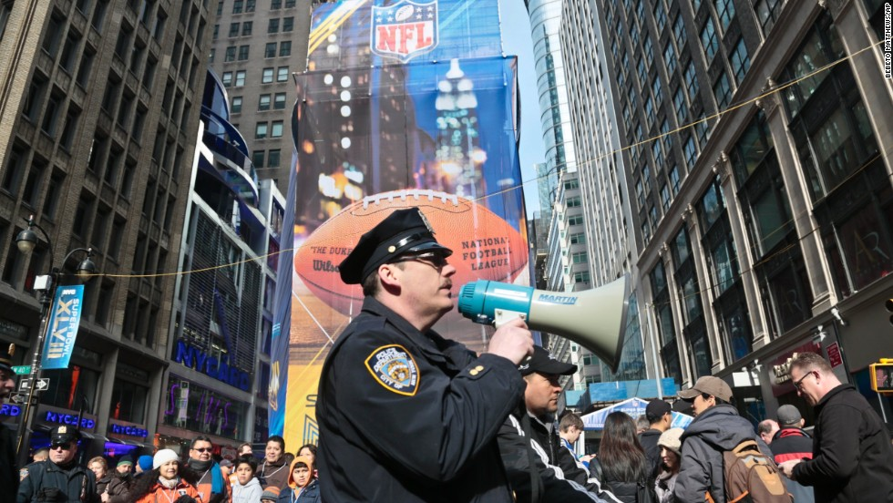 A New York City police officer use a bull horn to direct pedestrians visiting Super Bowl Boulevard on February 1 in New York.