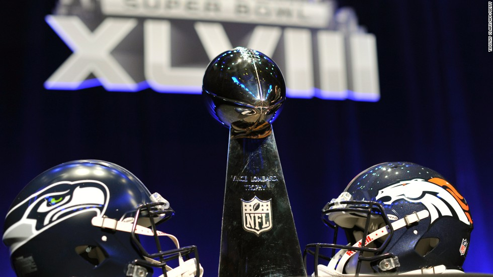 The helmets of the competing Super Bowl teams Seattle and Denver flank the iconic Vince Lombardi trophy.