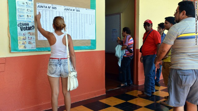 A woman looks for her name at a polling station in San Jose during the presidential election, on February 2, 2014. Costa Ricans choose a new president Sunday from a field of four candidates, none of whom have a clear lead in the polls and with nearly a third of voters undecided.