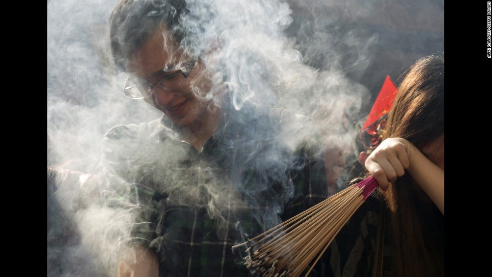 Smoke from burning incense sticks surrounds people as they mark the third day of the Lunar New Year at Che Kung Temple in Hong Kong on February 2.