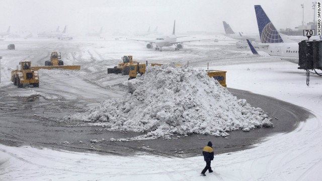 Plows clear runways as snow falls at Newark Liberty International Airport Monday, Feb. 3, 2014, in Newark, N.J. Air traffic is disrupted in Ohio, the Mid-Atlantic and the Northeast as another winter storm bears down on the eastern U.S., only a day after temperatures soared into the 50s. (AP Photo/Kiichiro Sato)