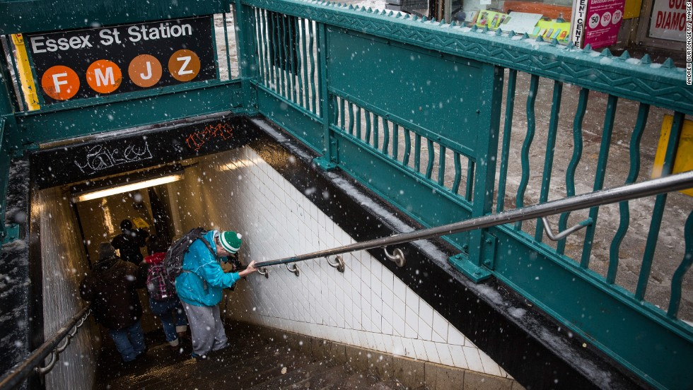 A man uses the handrail to get into a subway station February 3 on New York's Lower East Side.