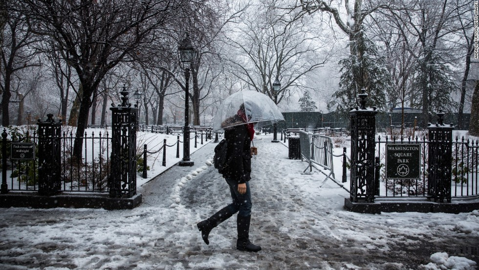 A woman walks through Washington Square Park as snow falls in New York on February 3.
