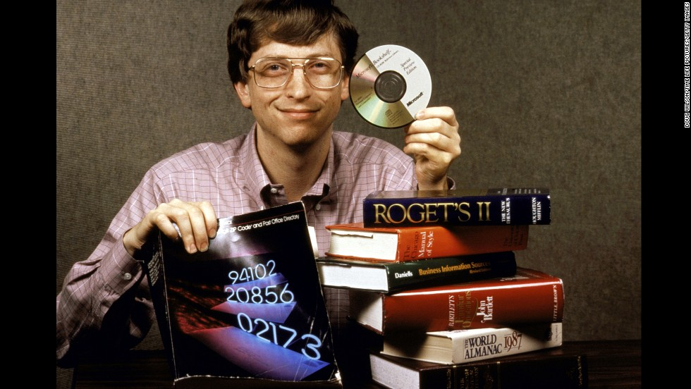 Gates holds up Bookshelf, a new compact disc for computers which holds all the information contained in the books pictured.
