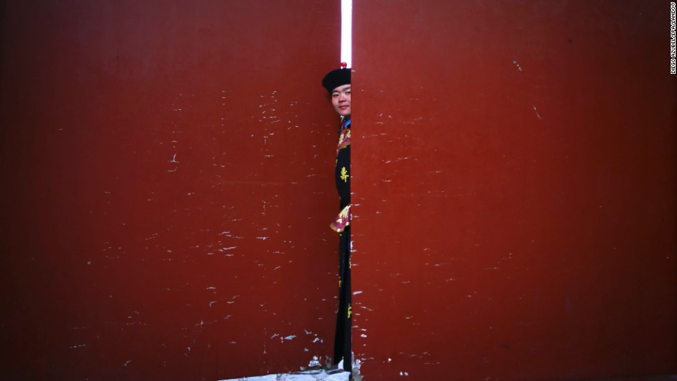 A performer peeks through a door before the start of a ritual at a temple in Beijing on February 4.
