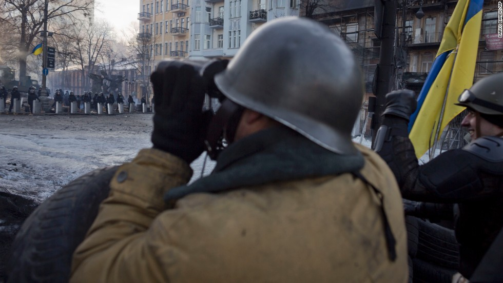 Protesters keep an eye on police February 4 as they man a barricade in Kiev.