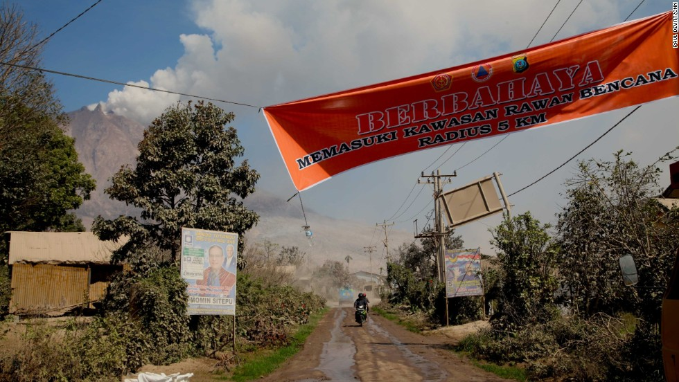 A banner shows the start of a 5 km exclusion zone around the volcano. Many people from villages closer to the summit continue to venture inside this zone. The 15 people killed on Saturday were from one of these villages.