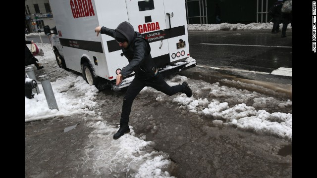 A man leaps over a slushy curb in New York City on February 5.