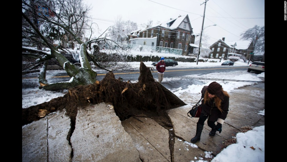 A woman ducks under a utility line next to a downed tree in Philadelphia on February 5.