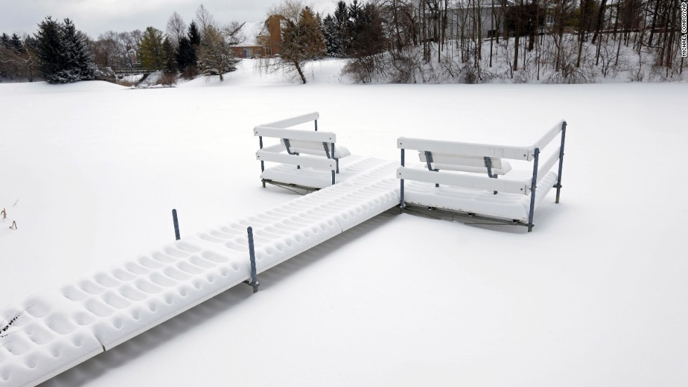 Snow piles up on a dock near a frozen pond in Carmel, Indiana, on February 5.