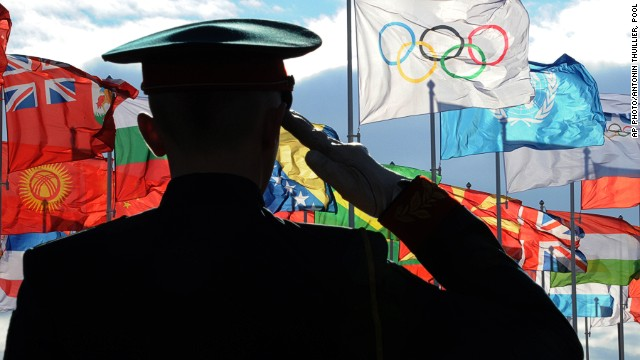A security guard salutes toward an Olympic flag and flags of the United Nations and countries participating in the 2014 Winter Olympics, Saturday, Feb. 1, 2014, in the Athletes Village in Sochi, Russia.