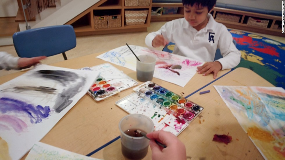 A pre-kindergarten student wears Google Glass while painting with watercolors for a community service project. He documented how crayon and watercolors interact, and the work was eventually sent to be place mats at a local Ronald McDonald House.