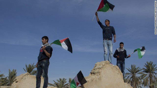 Activists wave Palestinian flags atop an abandoned house near Jericho.