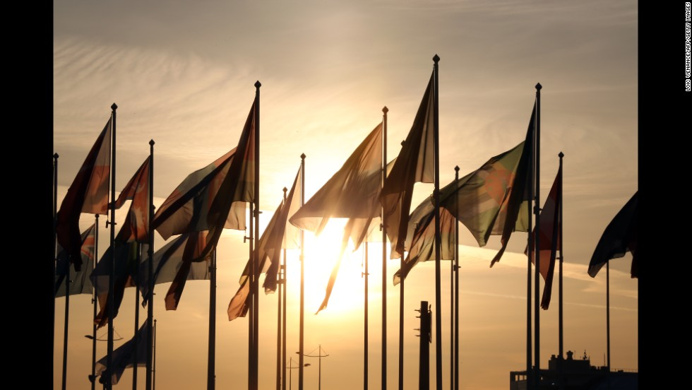 Before the start of the ceremony, the sun sets behind delegation flags.