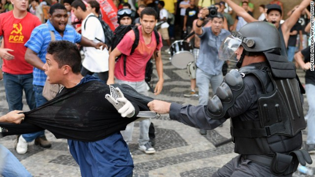 A member of the Special Police Operations Battalion (BOPE) holds a youngster during clashes with demonstrators who entered the train's Central Station in Rio de Janeiro, during a protest against a hike on bus fare, on February 6, 2014. As from February 8, the city of Rio de Janeiro will raise 25 cents on public bus fare.