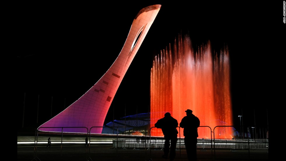Security personnel watch a practice run of a fountain show on the perimeter of the Olympic cauldron on Thursday, February 6.
