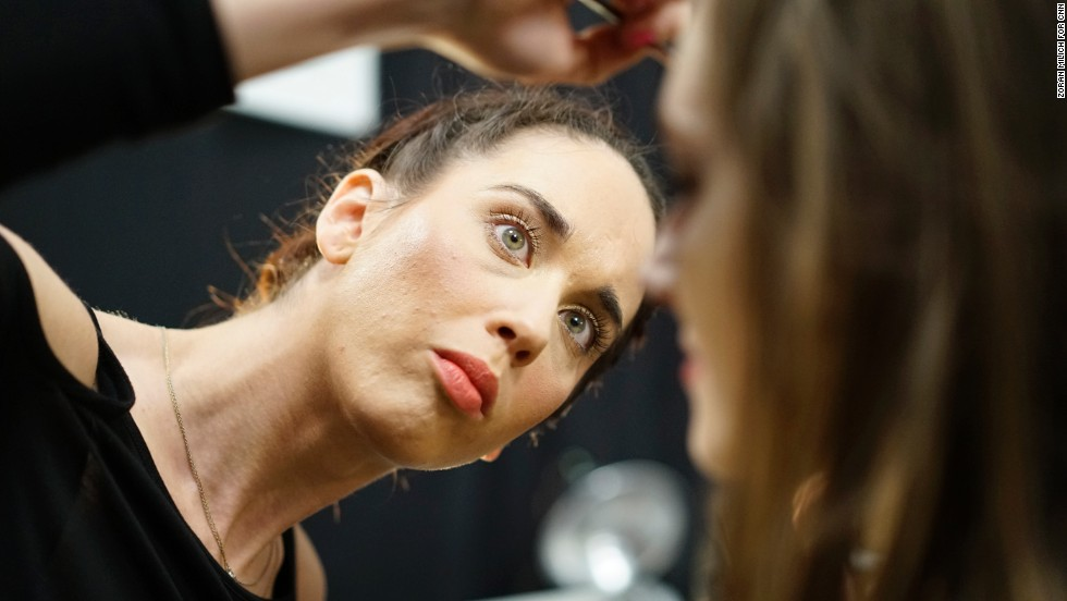 A makeup artist touches up a model before the Tadashi Shoji show.