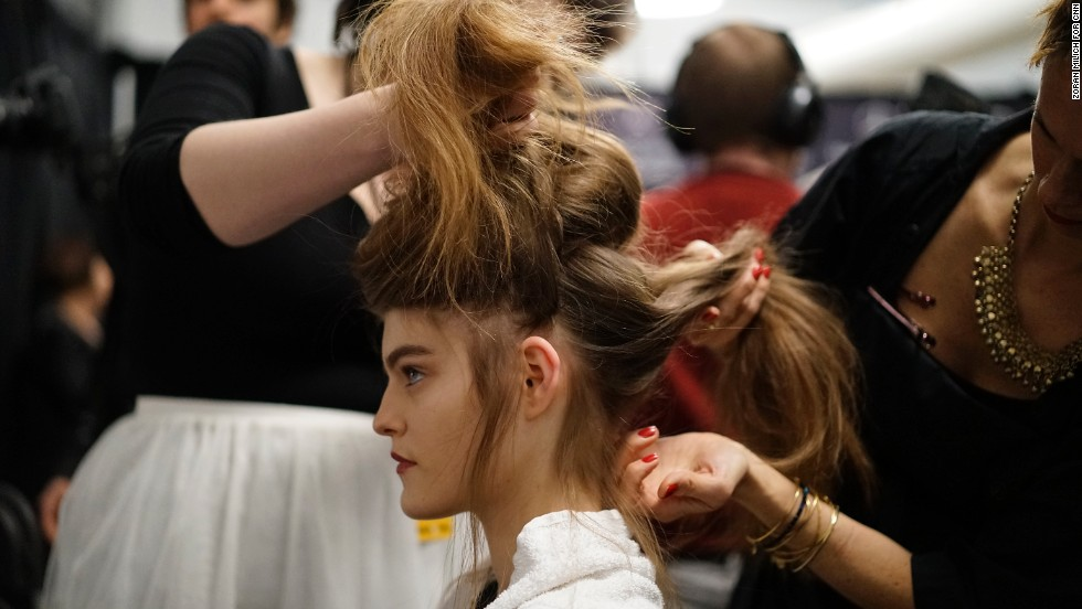 A model's hair gets pulled every which way to create a loosely braided updo for Tadashi Shoji's show.