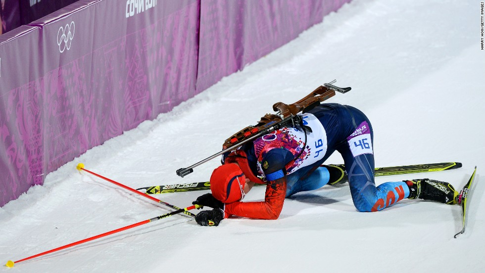 Dmitry Malyshko of Russia collapses in the snow after competing in the 10-kilometer biathlon sprint.